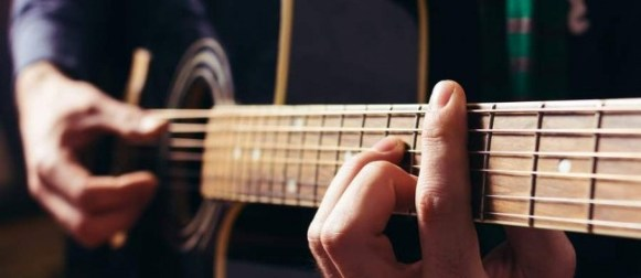 Man playing music at black wooden acoustic guitar.Focus on fingers.