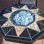 """Fire pit features granite tile uniquely cut w/ Fire Crystals.com in it."""
