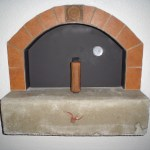 Red porcelain tile for the hearth w/ deco, concrete mantel and custom leasure Concepts patented door.
