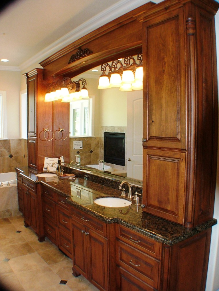 Custom bathroom cabinets with cabinets surrounding mirror.