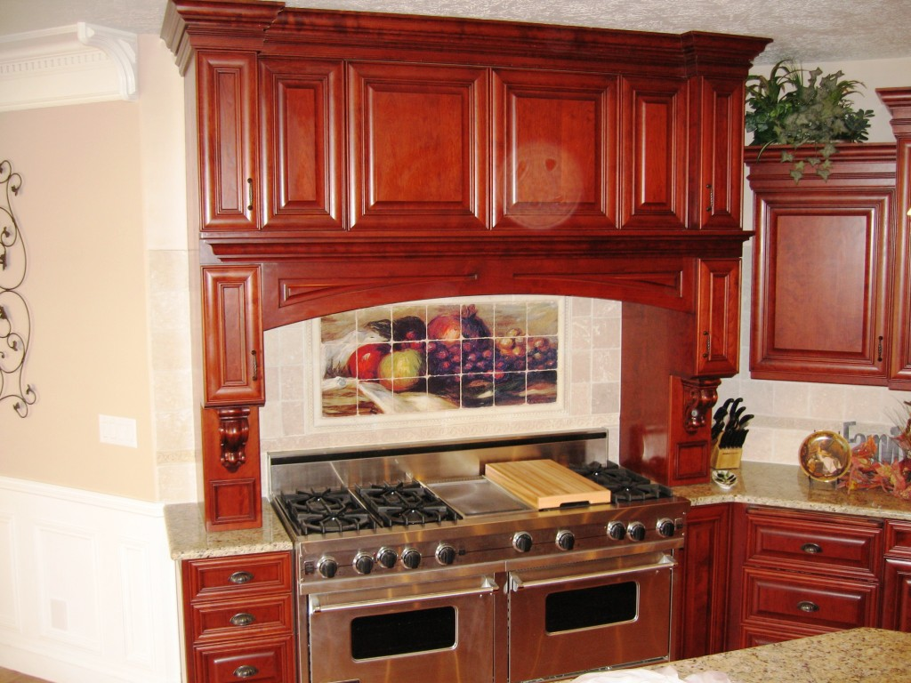 Double Range Hood with hidden pull out spice racks. Custom designed, built and installed for a private residence in Utah by Legacy Mill & Cabinet.
