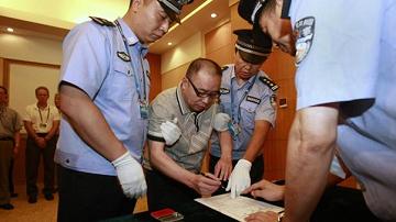 Lại Xương Tinh, giữa, được công an hộ tống khi ông ký vào lệnh bắt giữ ông tại phi trường quốc tế Bắc Kinh ngày 23-7-2011. (Xinhua/Reuters)