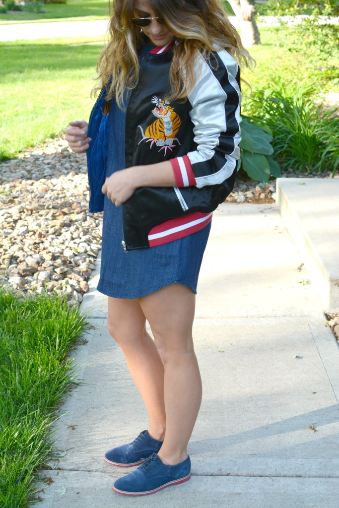 Ashley from LSR in a denim dress and silk souvenir bomber jacket