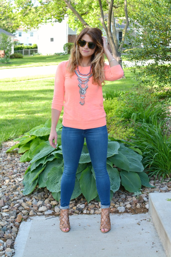 Ashley from LSR in a neon coral sweater and a silver statement necklace