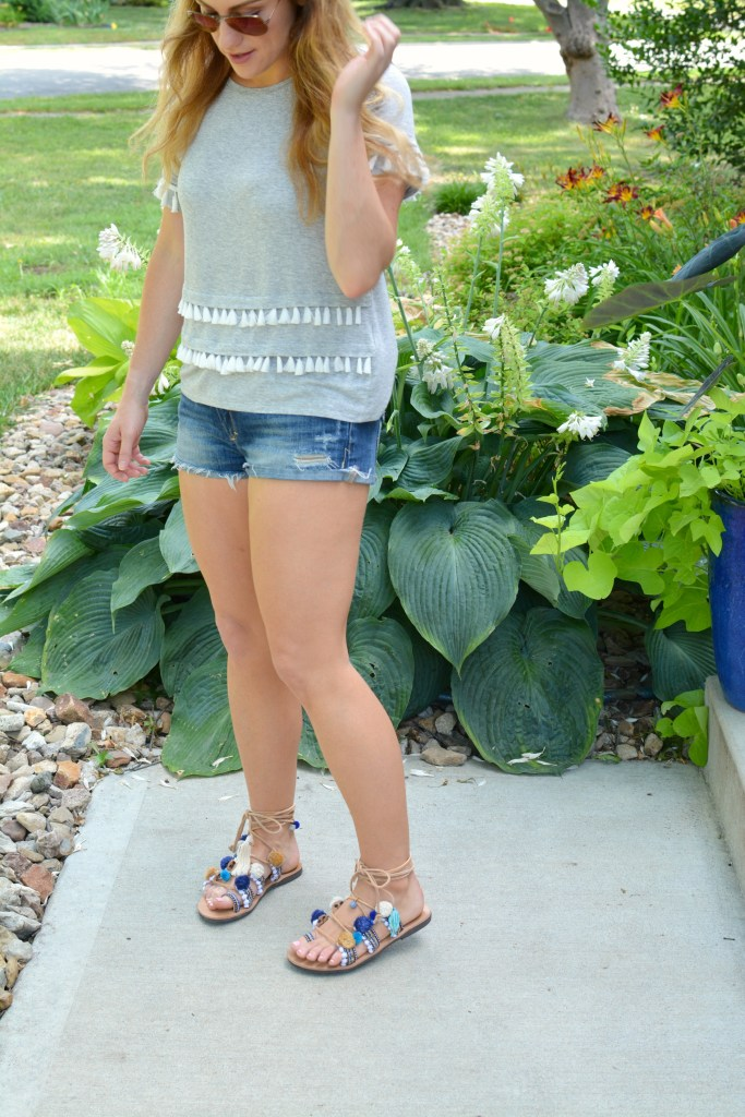 Ashley from LSR in a gray tassel tee, cutoff shorts, and pom pom lace-up sandals
