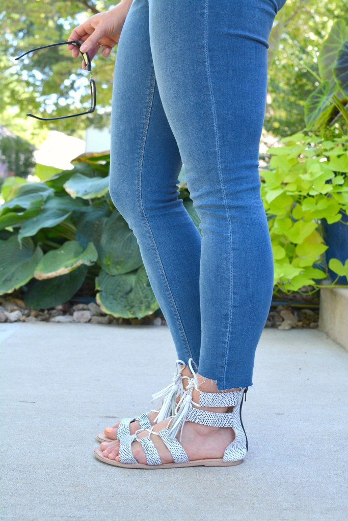 Ashley from LSR in stepped hem jeans and white lace-up sandals