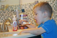 Three year old Logan Bonertz brushes his teeth with flouridated water.