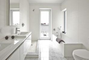Los baños cuentan con suelos de mármol blanco Carrera, pisos de amortiguación de sonido y bañeras cubiertas con roble blanco certificado por la Sustainable Forestry Initiative