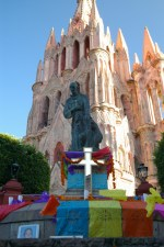 A statue of Fray Juan de San Miguel covered in colorful paper cut-outs forming an offering altar for the Day of the Dead (Dia de los Muertos). In background the Parroquia (parish church) in San Miguel de Allende, Mexico.