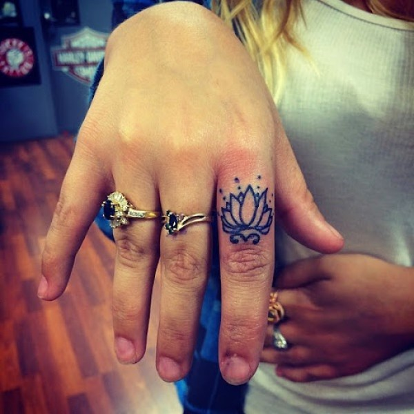 small lotus flower tattoo on finger