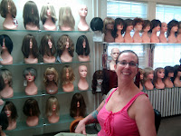 Trish surrounded by wigs.