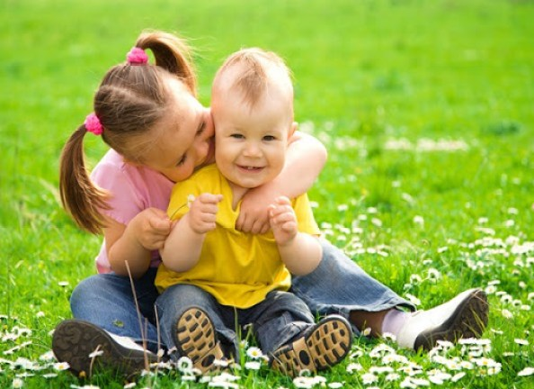 Two children sitting on green meadow