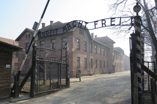 """Der Eingang ins Stammlager Auschwitz mit dem """"Arbeit macht frei""""-Schriftzug"""