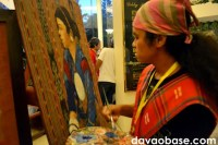 Ronald Tamfalan of the T'boli tribe paints on dagmay fabric, as part of the Kadayawan Fiesta at the Apo View Hotel