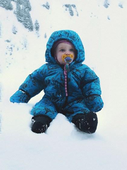 Selbstversorgerhuette in der Schweiz. Baby sitzend im Schnee.