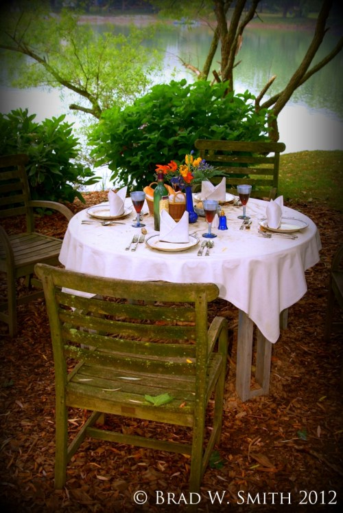 a round table with formal place settings for 4, in the woods, next to a blue lake