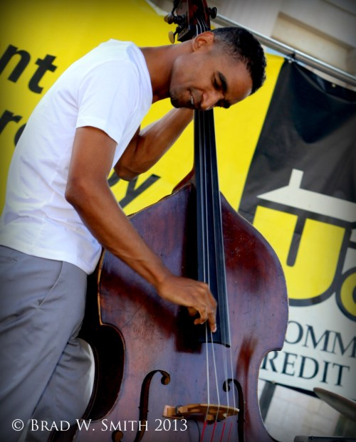 black man casually dressed, head tilted close to bass neck, plucking near end of fingerboard