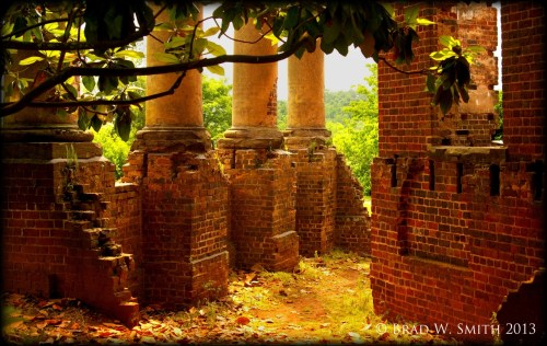 yellowed smooth pillars, each on a red brick foundation, crumbled brick, remains of a house