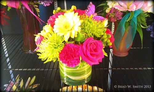 bouquet of pink, green and yellow flowers in a round glass bowl, in florist case