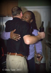 a hug of support between men, Brad W. Smith photographer Alt: White man, black man, in a hug of friendship in a private home.