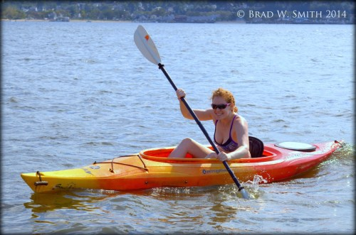 sunny day, young woman in shades, orange kayak, blue water