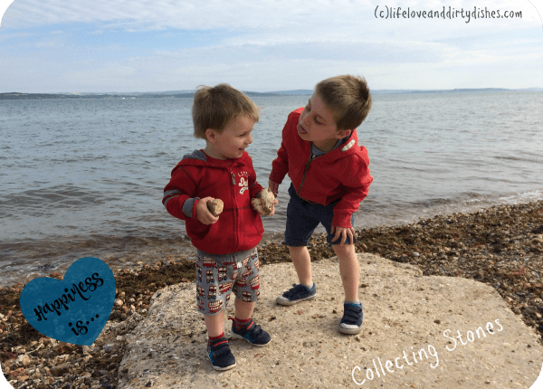 Image of two boys collecting stones at the beach