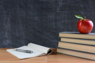 Closeup of a teachers desk with books, paper and pen and a red apple in front of a chalkboard. Horizontal format with copy space.
