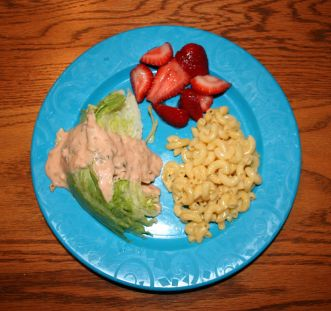 The plate on the picture is blue and has macaroni and cheese with a side of fresh sliced strawberries and the lettuce with a generous size serving of dressing on top.