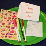 Shows a tray with stickers, pens, pencil, class list, and blank Valentine's Day cards on it.