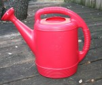 Image shows a red plastic watering can with a sieve nozzle.