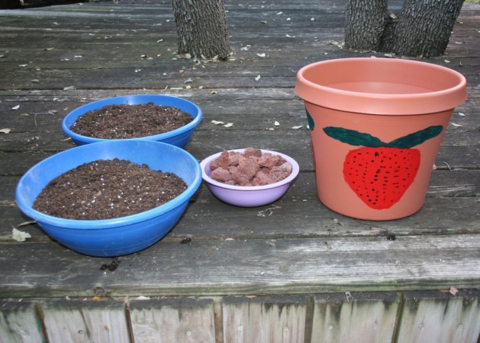 Image shows large decorated pot, 2 large bowls of soil and a small bowl filled with small rocks.