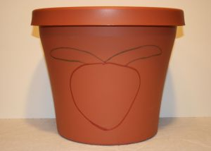 Image shows a large plastic, clay-colored pot with an outline of a strawberry on it.