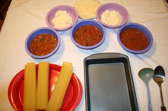 Image shows proper lay out of ingredients for a child to assemble a lasagna successfully.