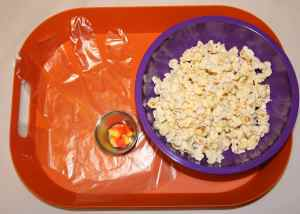 Image shows a bowl of popcorn, a small container with candy corn, a twist tie, and a food service glove on an orange tray.
