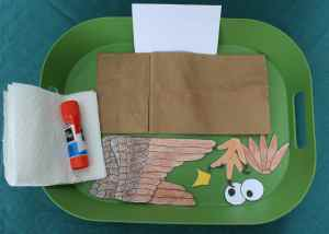 Image shows a green tray with a brown paper lunch bag, a white piece of card stock, cut out wings, beak, feet, crest and eyes along with a glue stick and paper towels.