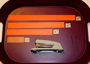 Image shows a purple tray with different size strips of construction paper labeled by length, two bobby pins, and a stapler.
