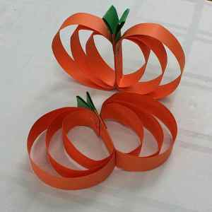 "Image shows two small pumpkins made out of 1"" wide strips of orange construction paper."
