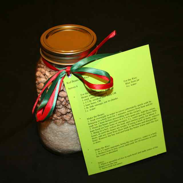 Image shows a large mason jar filled with beans and rice, with a colorful ribbon holding the instructions for making red beans & rice.