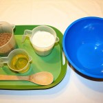 Image shows a green tray with All-bran cereal, flour, oil and a wooden spoon on it next to a large blue bowl.