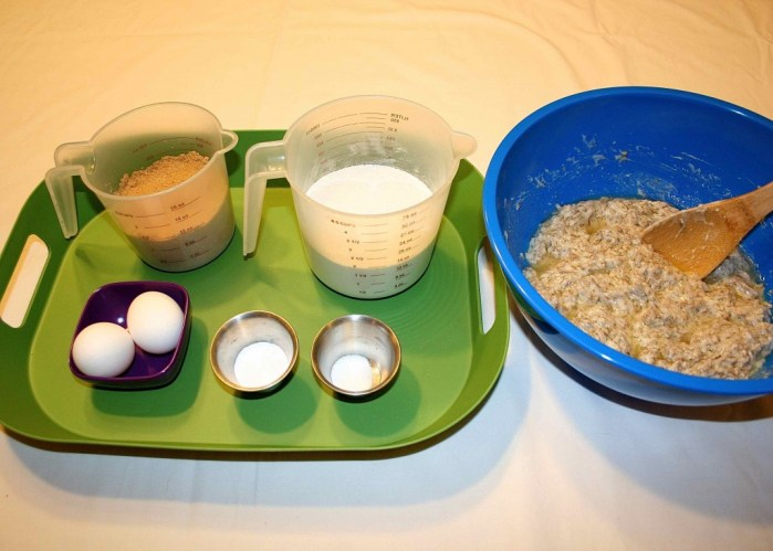 Image shows a green tray with measured brown sugar, flour, 2 eggs, baking soda, and salt next to a large bowl with some batter mix and a spoon in it.