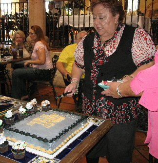 Publisher Grace Anne cutting the cake