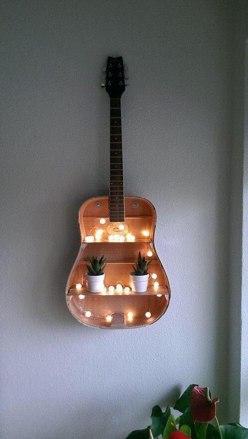 en-gammel-gitar-pa-veggen-med-lys-i-diy