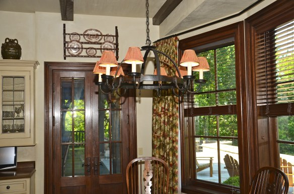 The breakfast areas includes an iron chandelier and a plate rack over the door