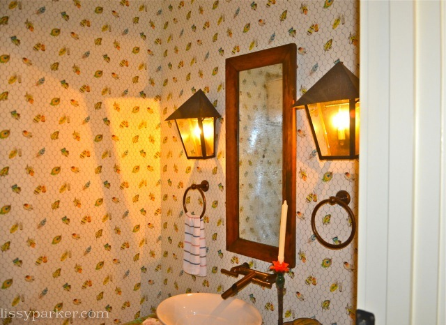 Powder room has charming lantern sconces—love the towel rings on both sides