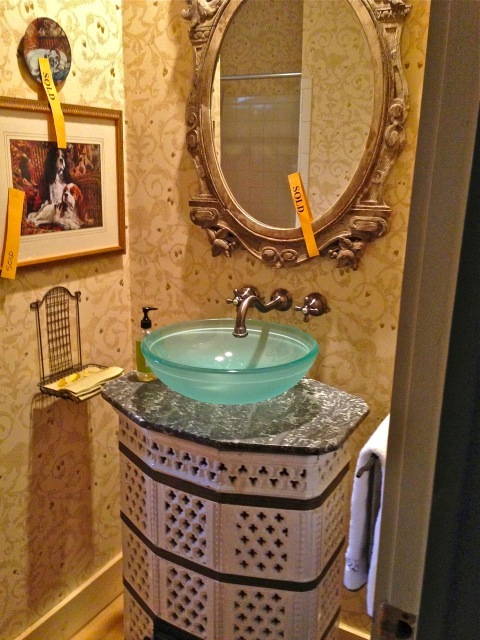 This French stove became a sink base for the half bath—notice the wall tray holding the towels