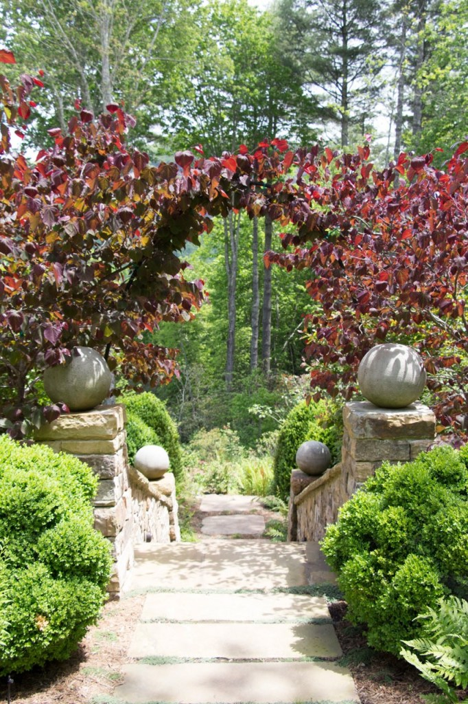 Stone walls and steps lead through the cloud boxwood and tree arch