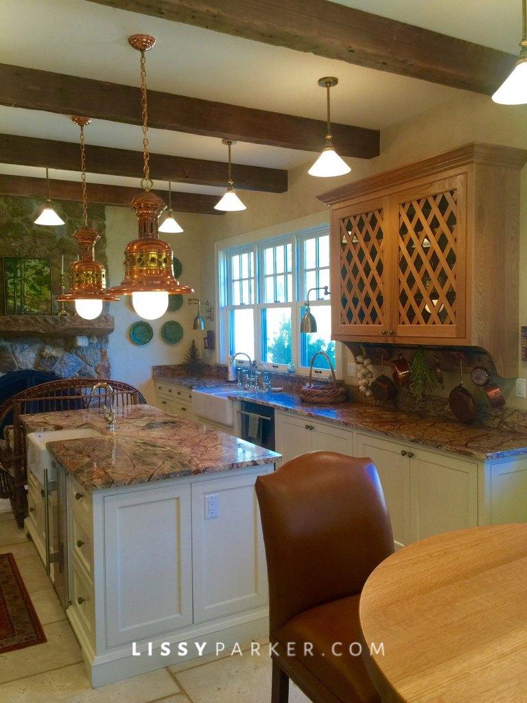 Lattice front cabinets, English lanterns and a farm sink under three windows—fabulous