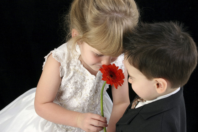 Adorable Young Children Smelling Daisy Together
