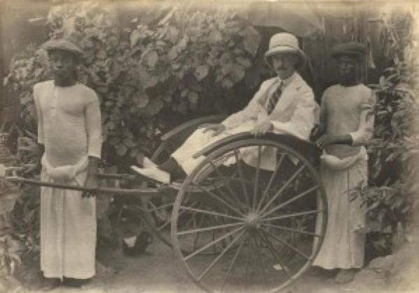Osborne in a rickshaw, with boys besides him, Lagos c.1910-13