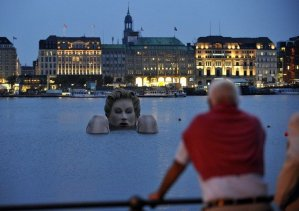 142974-man-looks-at-a-mermaid-sculpture-created-by-oliver-voss-in-the-late-ev